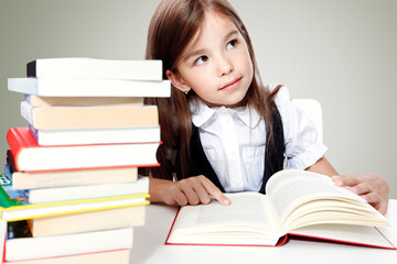 Young cute girl sitting at the table and reading a book