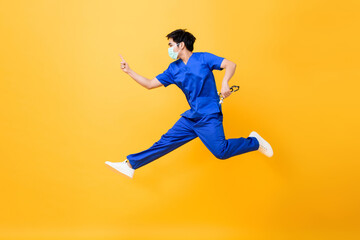Young Asian male doctor wearing medical mask jumping and pointing hand up isolated in yellow studio background