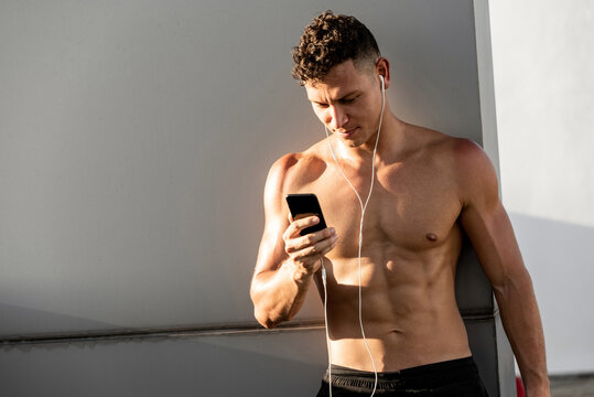 Shirtless handsome sports man wearing earphones listening to music from mobile phone relaxing after workout in open air