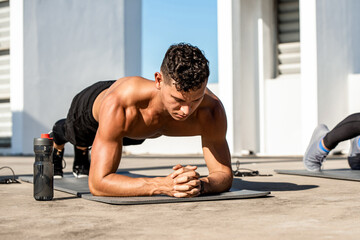 Muscular sports man doing plank exercise in the open air on building rooftop