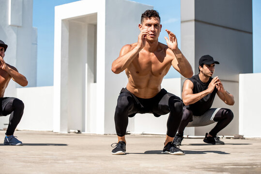 Group of fit sports men doing squat bodyweight workout training outdoors on building rooftop - exercise in the open air concept