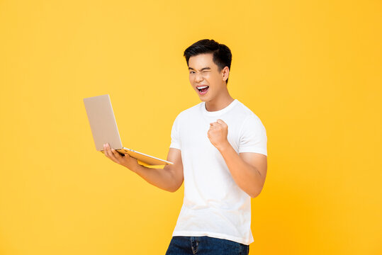 Portrait of a smiling  young handsome Asian man holding laptop while doing a winning closed fist gesture in isolated studio yellow background