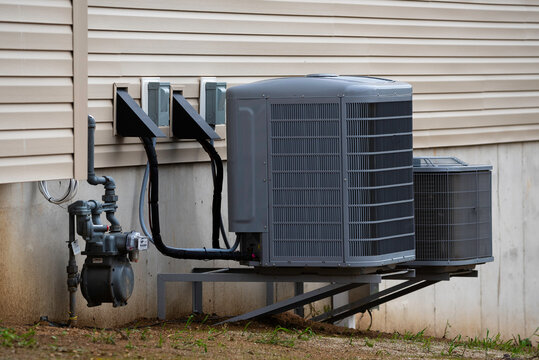 Air conditioning unit on concrete slap with new construction brick house cold building