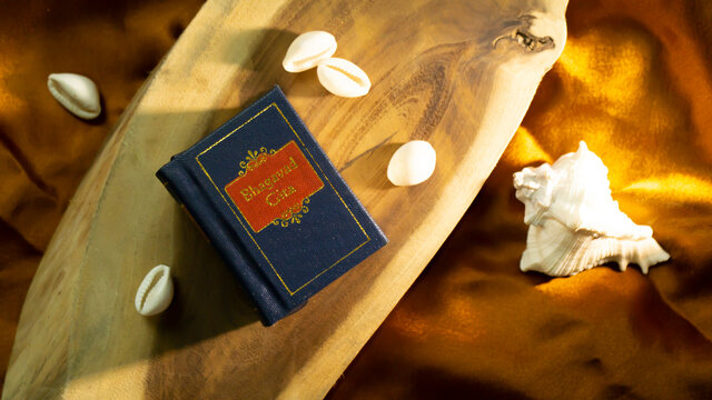 Hindu holy book and cowrie shell on a wooden surface with golden satin cloth