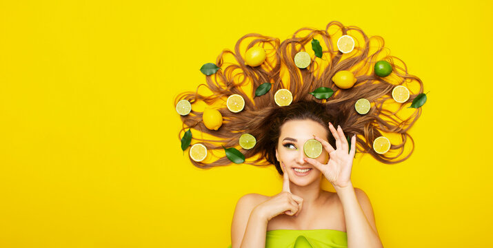 beautiful girl lying on yellow background with citrus fruits in long hair,young woman head with lemon slices and leaves thinking
