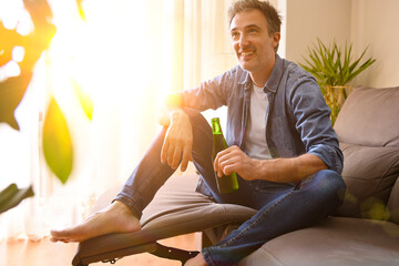 Relaxed man with a beer resting at home