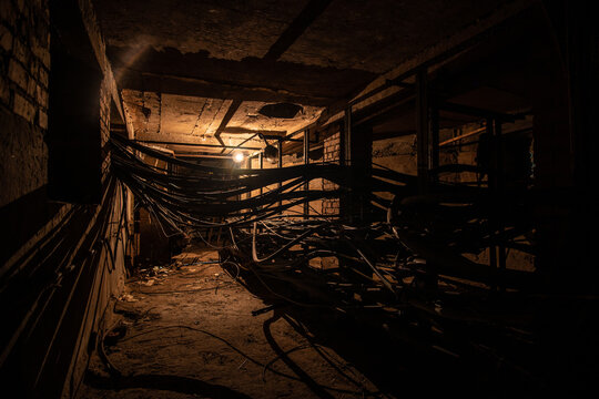 An old underground brickwork cable tunnel or basement with cables with tungsten lamp lighting.