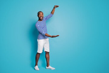 Full length photo of candid funky afro american guy hold hand show big size measurement object wear nautical vest sneakers isolated over blue color background Papier Peint