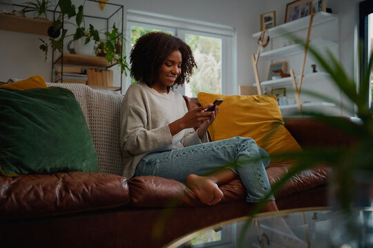 Happy young african woman using mobile phone while sitting a couch at home