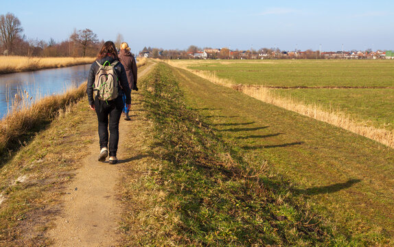 Group of hikers walking on a dike  along a canal on a sunny winter day in the Netherlands