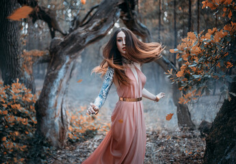 Fantasy portrait of a young red-haired woman in the autumn forest. The nymph girl runs and looks around. Long hair flying in the wind in motion. Background is nature dark trees, orange leaves falling