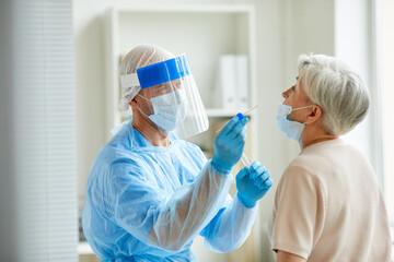 Modern laboratory worker wearing personal protective equipment testing senior woman for coronavirus using nasal swab method