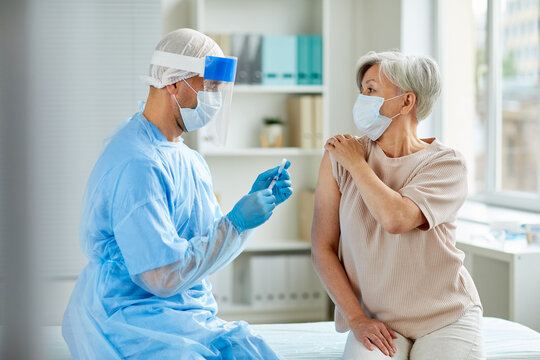 Side view shot of male nurse wearing protective mask and gloves preparing medical syringe for giving injection to senior patient