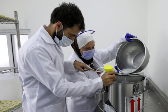 Salma Zu'bi, founder of the Atan soap brand, and her son Imad mix ingredients used to make their soap, at Salma's lab in Amman