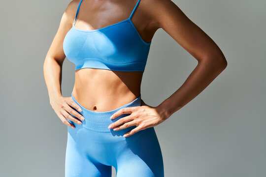 Cropped image of fit woman torso  on grey background