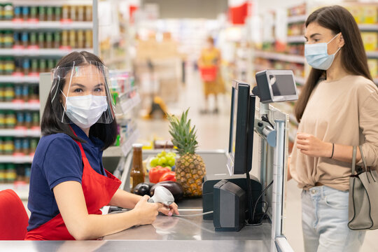 Modern store worker and customer following personal protection rules during Covid-19 quarantine days, wearing masks