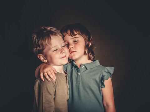 preciosos hermanos mellizos rubios divirtiendose en una sesion de fotos de estudio