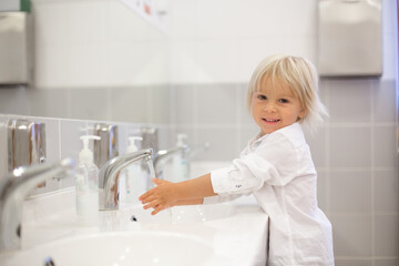 Little preschool child, blond boy, washing hands in bathroom in kindergarden