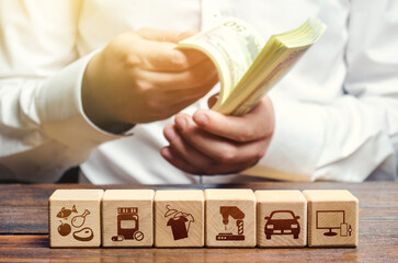 A man is counting money on the background of blocks with goods attributes. Import and export of goods and products. Retail and sales. Trade surplus, high purchasing power. Economic recovery.