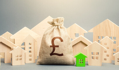 British pound sterling money bag and a city of house figures. City municipal budget. Buying real estate, fair price. Development, renovation of buildings. Investments. Cost of living. Property tax.