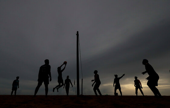 Sri Lankan youth play volleyball in the evening as rain clouds gather above them, in Colombo