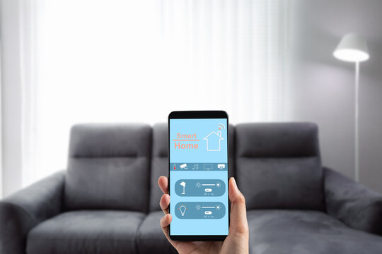 hand holding mobile phone with smart home screen