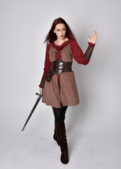 Full length portrait of girl wearing medieval costume. Standing pose holding a sword,  isolated...