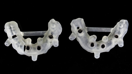 two surgical dental guides for large implantation of the upper and lower jaws, top view on a black background
