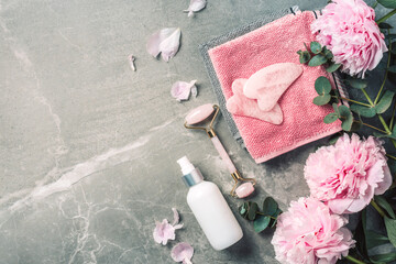 Cosmetic products bottles, towels, oil, face roller and gua sha massager, pink peonies flowers on marble background. Banner. Top view. Spa relax, body treatment, spa, skin care concept