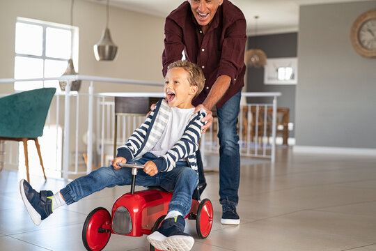 Playful grandfather pushing grandson toy car