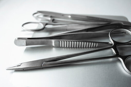 Surgical instruments on metal tray. Scalpel, clamp, scissors, surgical forceps on white background. Medical instruments