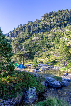Tent next to glacial river in mountain landscape near refuge Wallon Marcadau in French Pyrenees, France, Europe