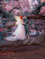 Young couple in love. A man and a woman are hugging on a huge tree. Themed creative wedding bright fantasy photography. Fairy woman in long pink dress with bright golden wings. A man in an elf costume