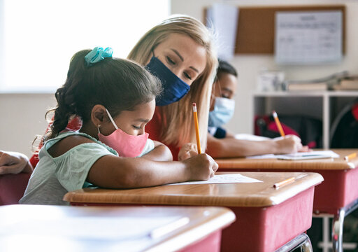 School: Teacher With Mask Helps Student With Math Sheet
