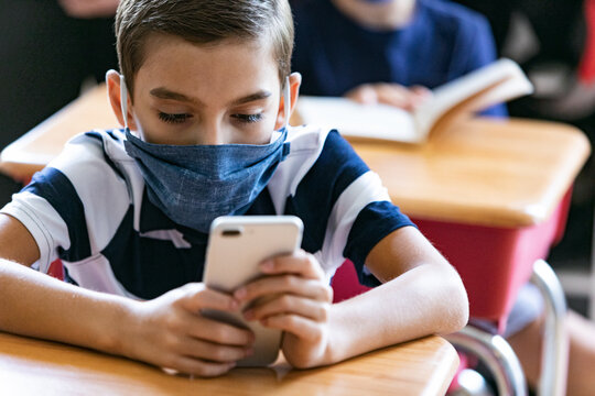 School: Student Wearing Face Mask Checks Cell Phone At Desk
