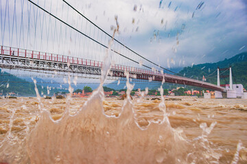 view of River Ganges, the famous bridge Janki Bridge during monsoon in Rishikesh, India