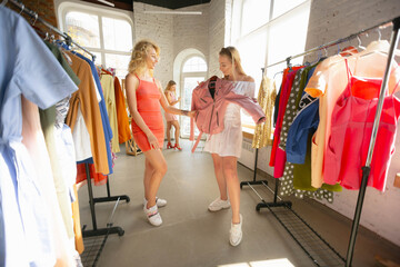 Summer collection. Wear, clothing shop during sales, summer or autumn collection. Young women looking for new attire. Concept of fashion, style, offers, emotions, sales, purchases. Brand new shopping.