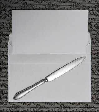 Blank paper with knife and letter lies on pattern. A top down view of a white envelope and a letter opener on a paper surface.