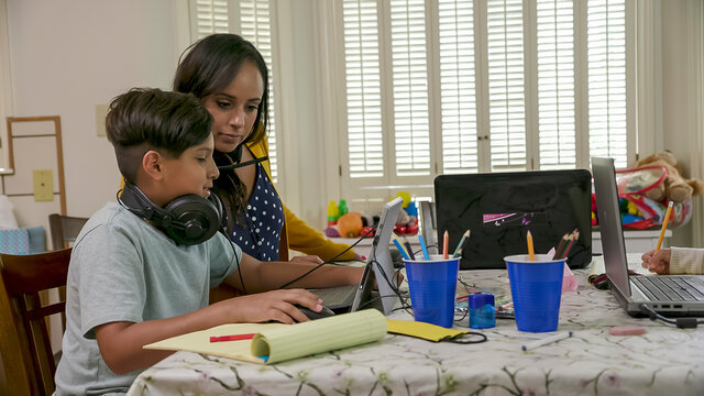 Work from home mom helps son with virtual learning due to school closures