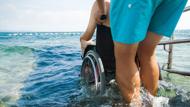 Disabled man at beach swimming on a wheelchair with assistance help on an accessible ramp.