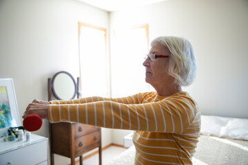 Senior woman exercising with dumbbells in bedroom