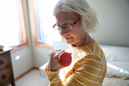 Senior woman exercising with dumbbell in bedroom