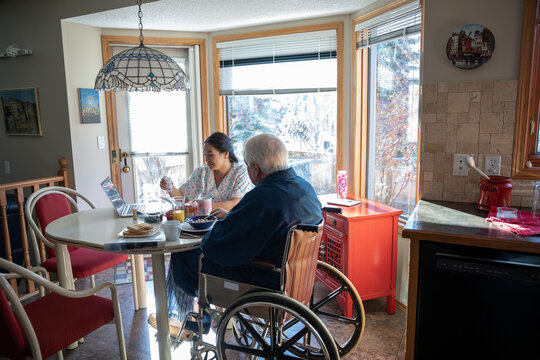 Home caregiver helping senior man in wheelchair at kitchen table