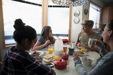 Soldier father and family eating breakfast at dining table