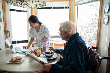 Home caregiver helping senior man with medication at breakfast table