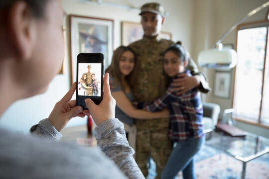 Woman photographing soldier husband hugging daughters at home