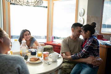Affectionate army soldier father and daughter hugging at table
