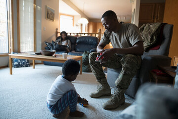 Soldier father and toddler son playing in living room