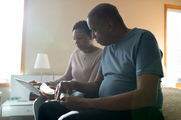 Mature couple with digital tablet and pill box on bed