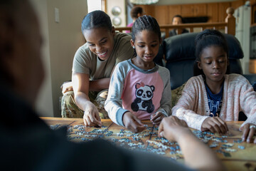 Mother and daughters assembling jigsaw puzzle at coffee table